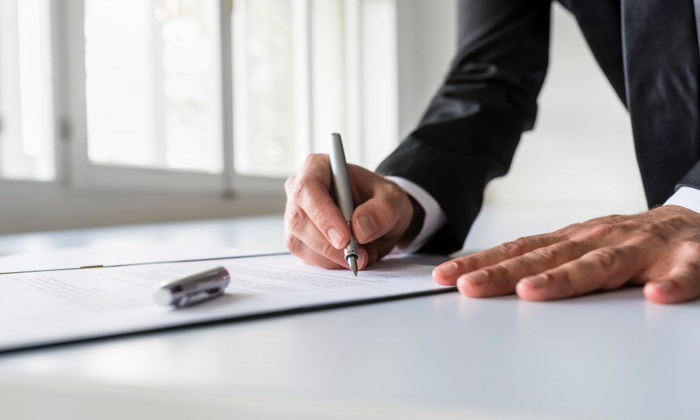 Businessman in office signing contract 3fja6vw min 1000x600